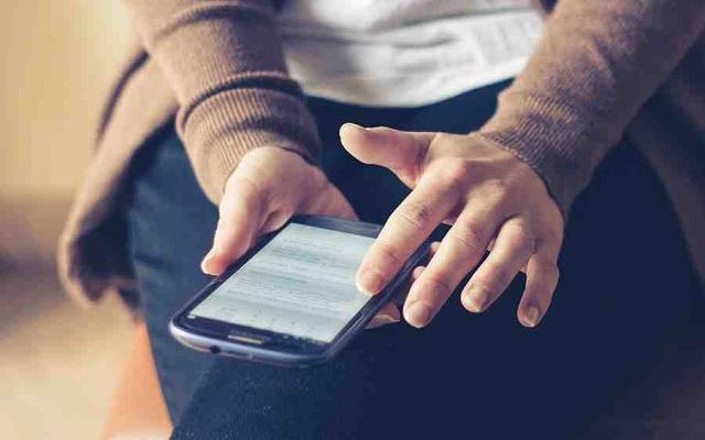 女性がスマホで出会い系サイトに登録しているイメージ